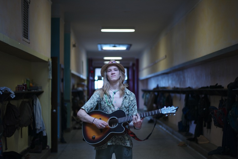760 kid with guitar in hallway